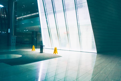 Yellow Wet Floor Signages Near Glass Wall