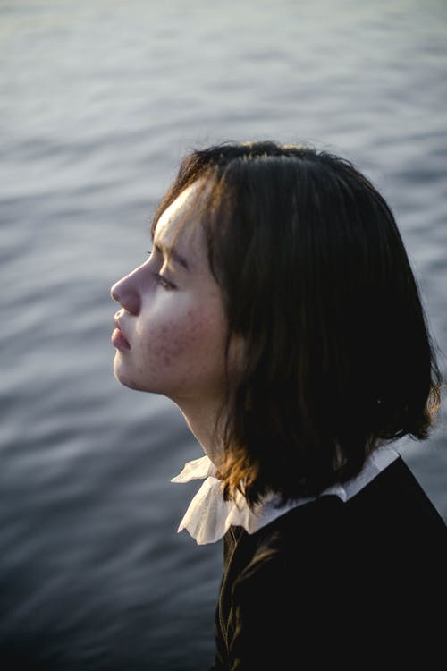 Side view of young woman sitting on river shore and looking at calm water surface