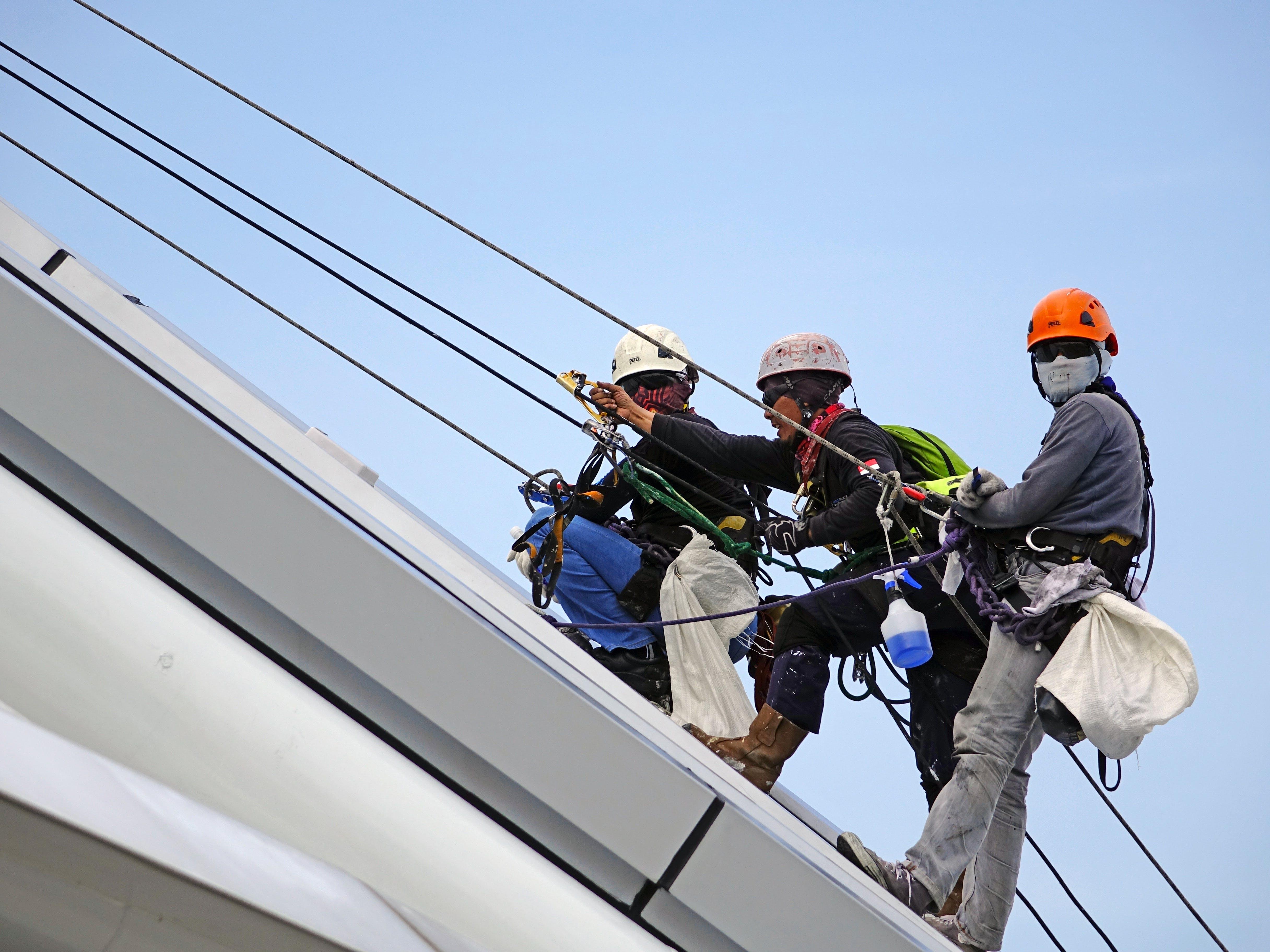 Three Men Climbing on Wall Using Rope