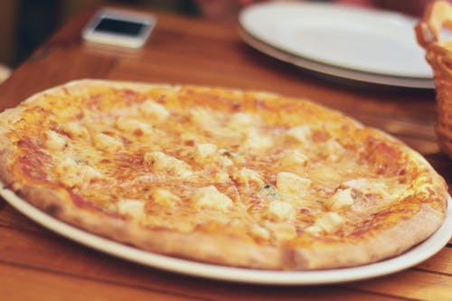 Close-up Photography of Pizza on White Ceramic Plate