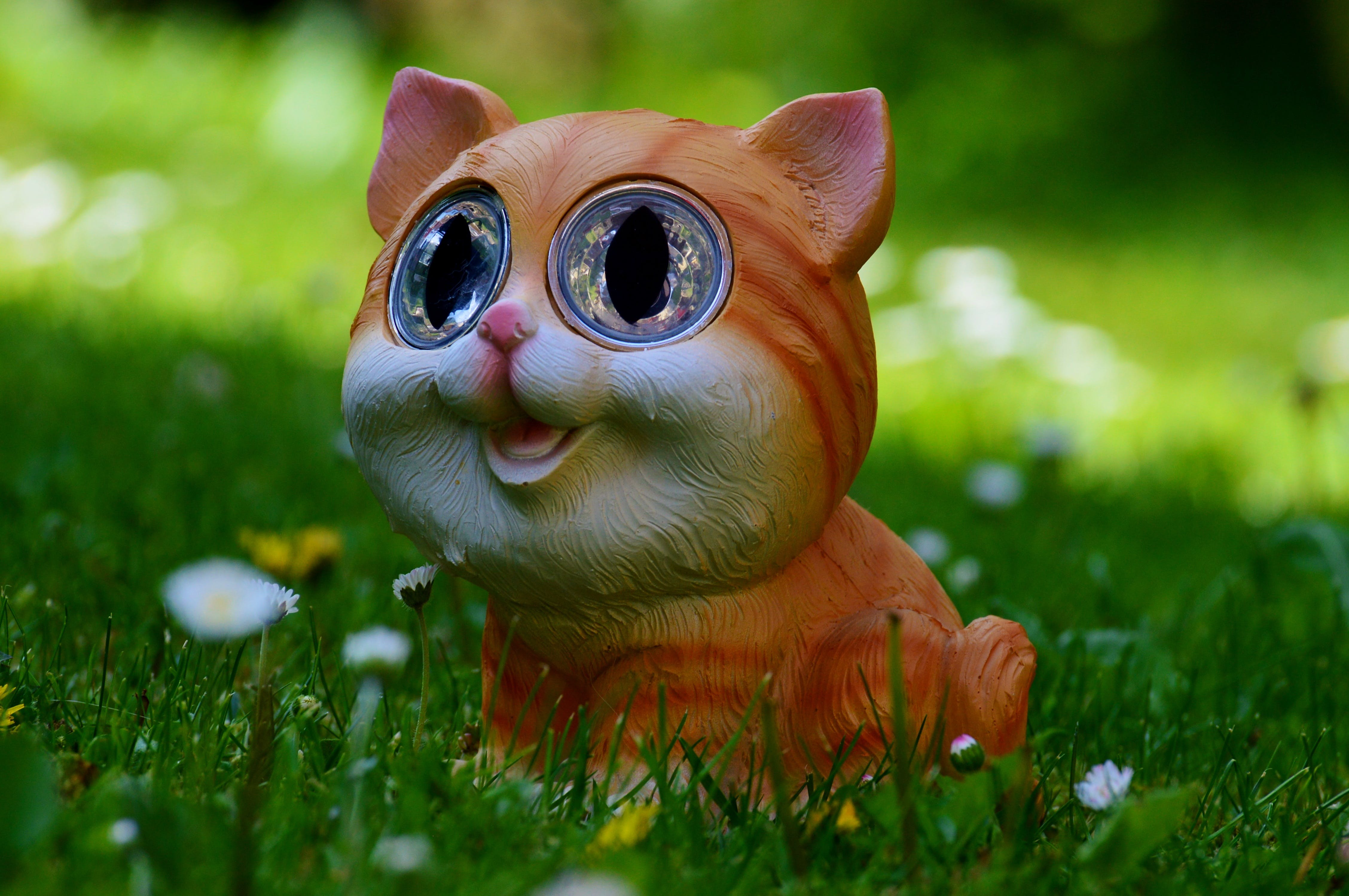 Yellow and Orange Tabby Kitten Figurine on Green Grass Plant
