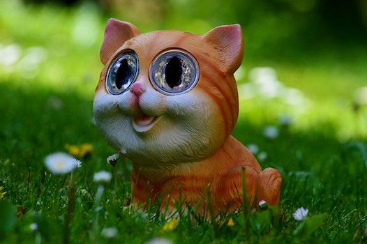 Yellow and Orange Tabby Kitten Figurine on Green Grass Plant