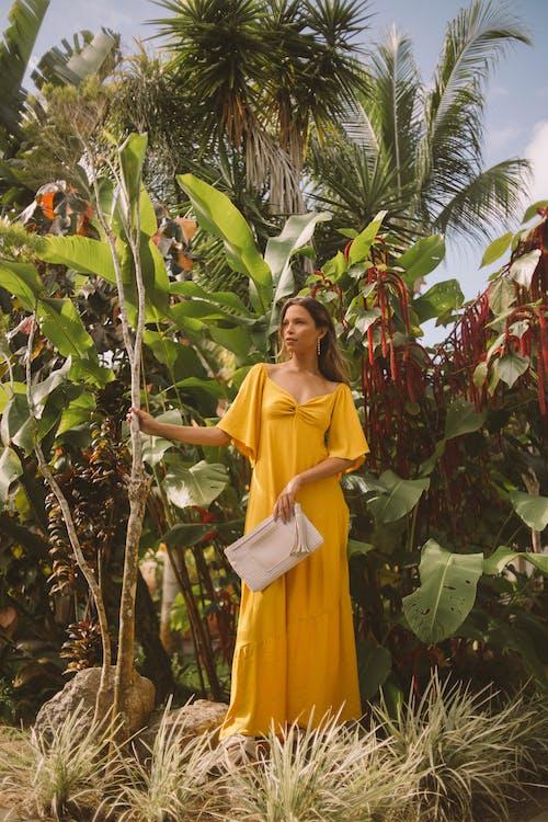 Безкоштовне стокове фото на тему «дивитися вбік, жінка, жовта сукня, заводи»