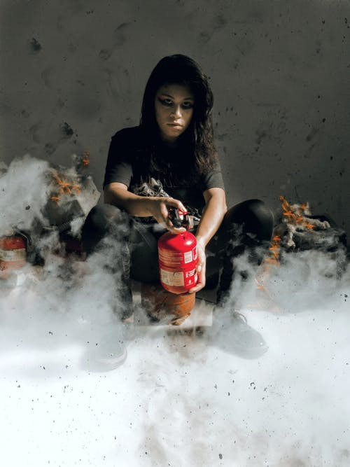 Woman in Black Shirt Holding Red FireExtinguisher