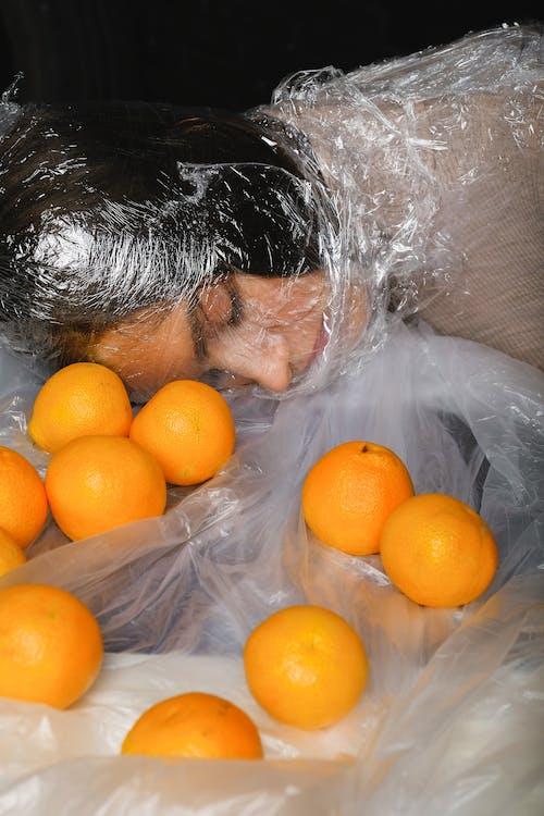 Безкоштовне стокове фото на тему «апельсини, екологія, жінка, забруднення»