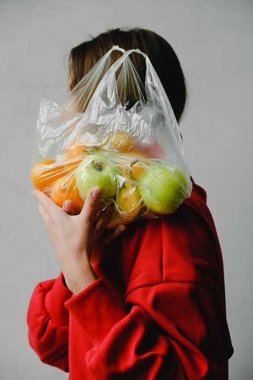 Person Carrying A Plastic Bag Full Of Fruits