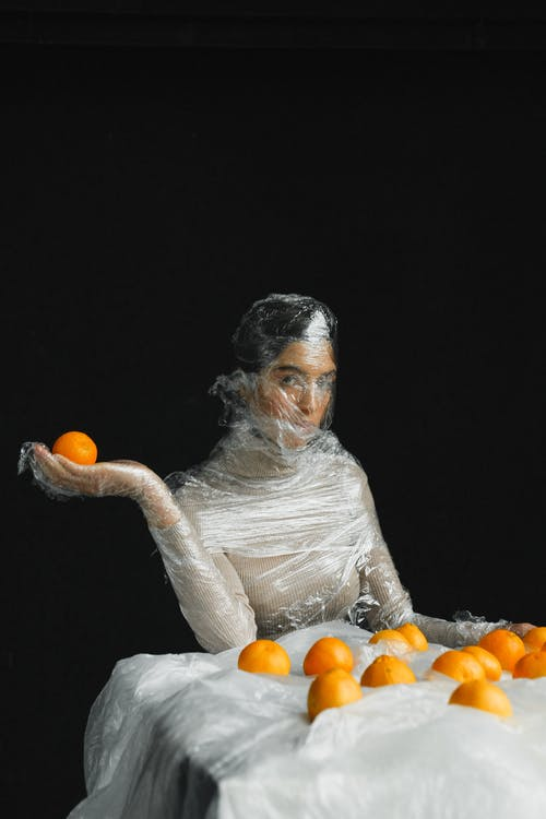 Woman in White Long Sleeve Shirt Holding Orange Fruit
