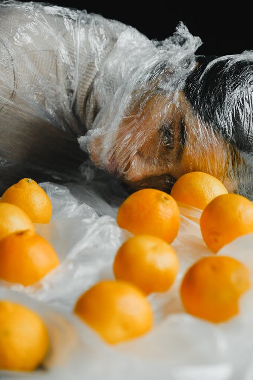 Orange Fruits in Front of Woman Covered with Plastic