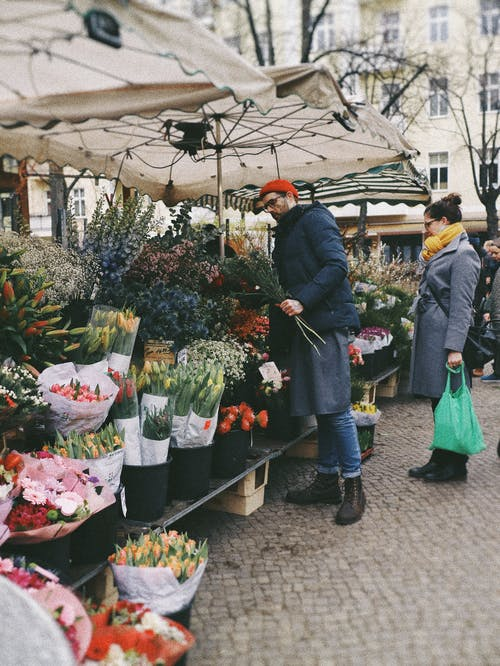 Man in Black Jacket and Blue Denim Jeans Buying Flowers