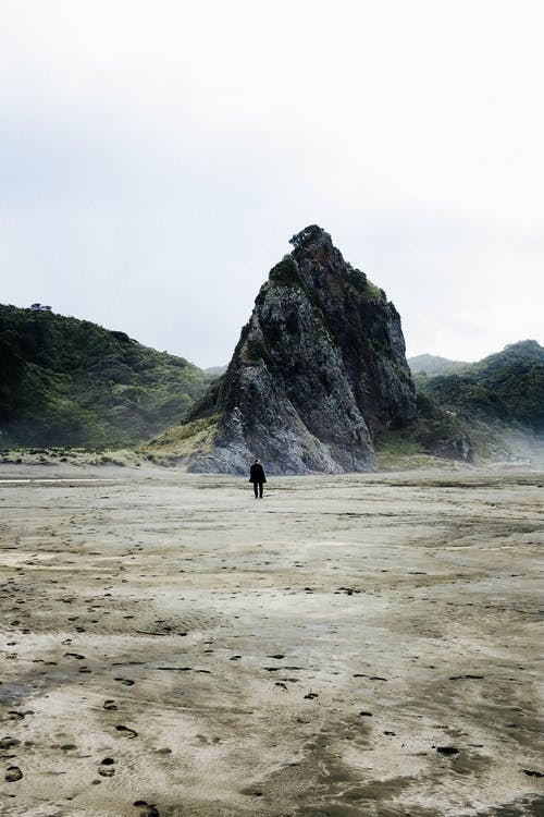 Person, Die Auf Strand Nahe Grünem Berg Geht