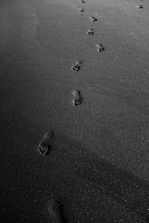 Grayscale Photo of Footprints on Sand