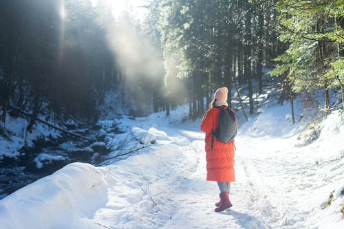 Girl in Red Jacket Standing on Snow Covered Ground