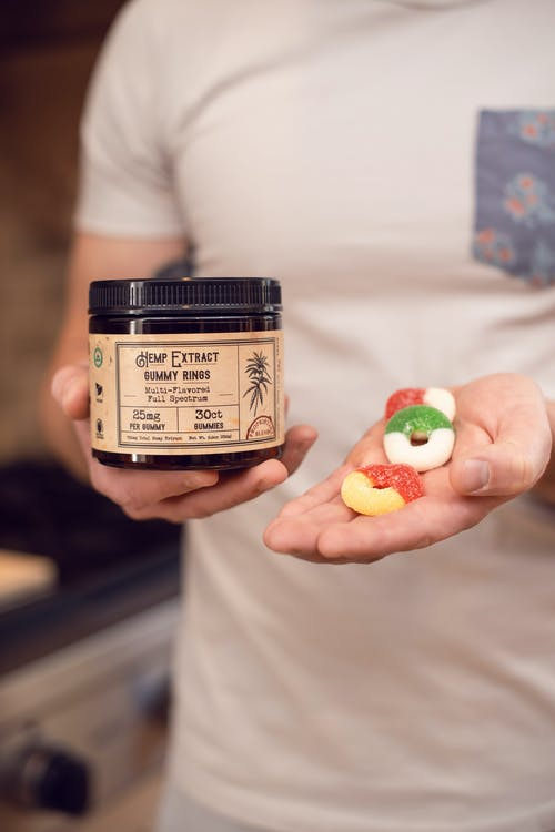 Person Holding A Jar And Gummy Candies