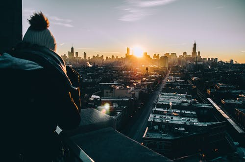 Man in Black Jacket Standing on Top of Building during Sunset