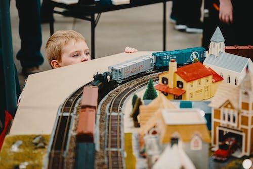 Boy Standing Beside A Train Toy