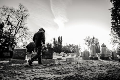 Monochrome Photo of Man Walking in Cemetery