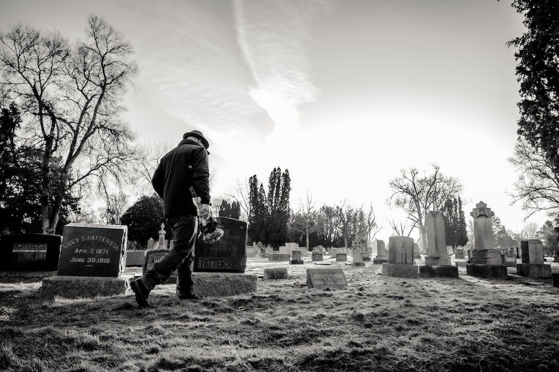 Monochrome Photo of Man Walking in Cemetery