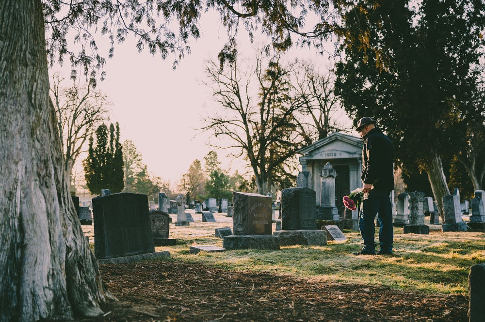 Man standing in front of a grave. | Photo: Pexels