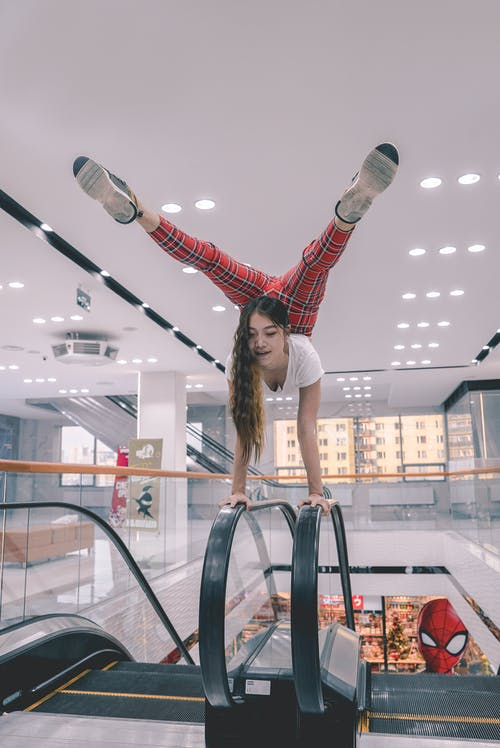 Woman In Red Pants And White Top Balancing On An Escalator