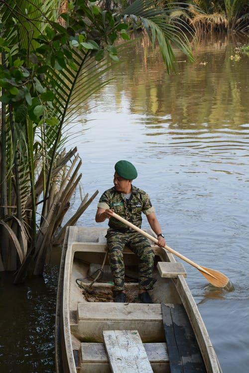 Man In Green Army Clothing Riding A Boat