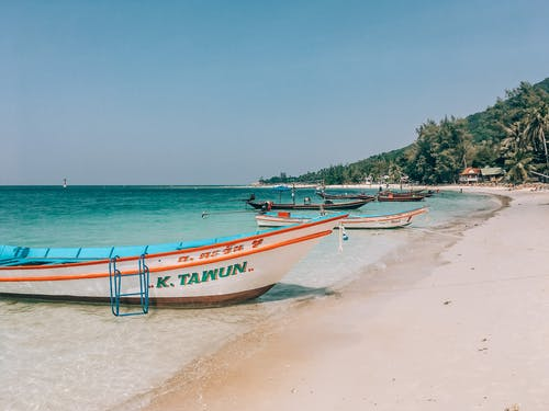 White and Blue Boat on Beach