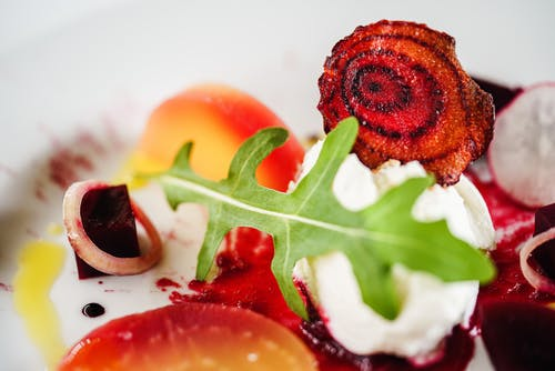 Sliced Beetroot On a Plate topped with Green Leaf