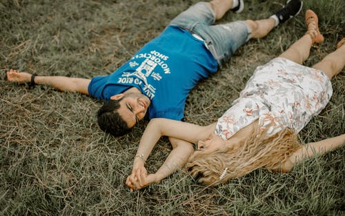 A Romantic Couple Lying On Grass