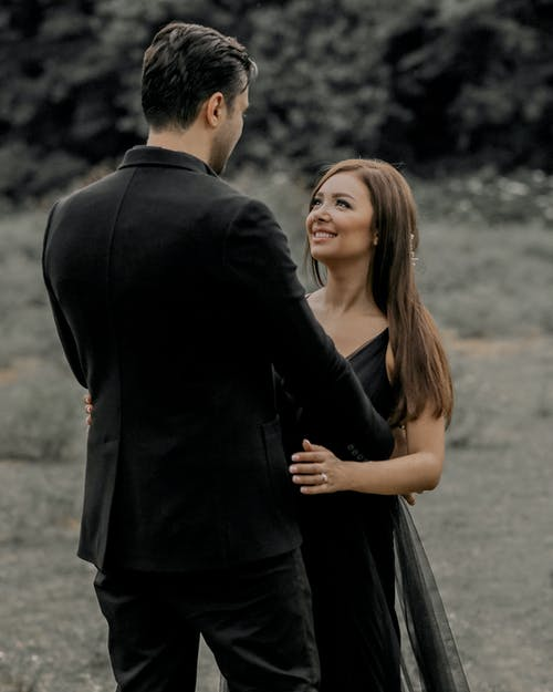 Man In Black Long Sleeved Coat And Woman In A Black Dress