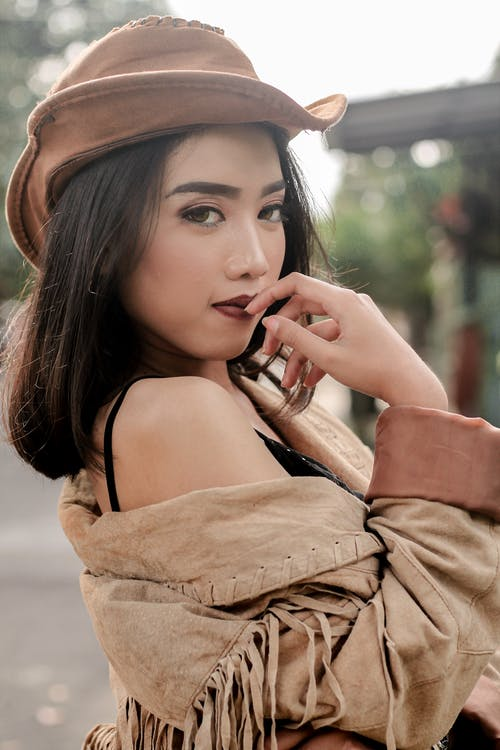 Woman in Brown Off Shoulder Dress Wearing Brown Hat