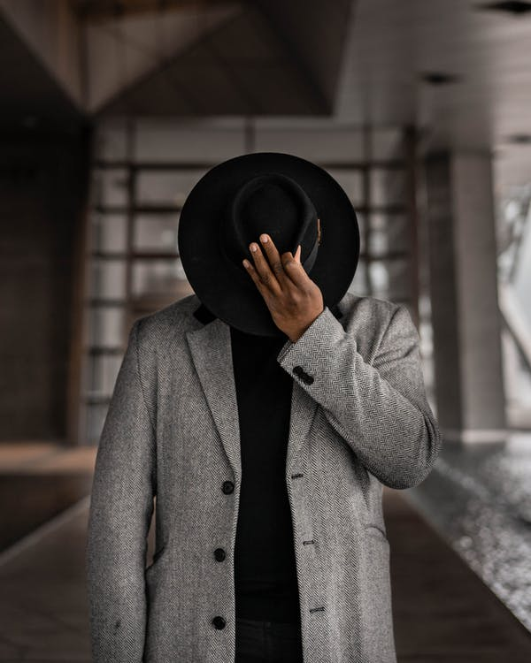 Person in Gray Coat Holding Black Hat