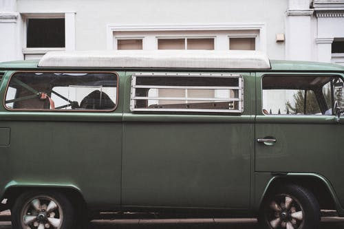 Green and White Volkswagen T-2 Parked in Front of White and Brown Concrete Building during