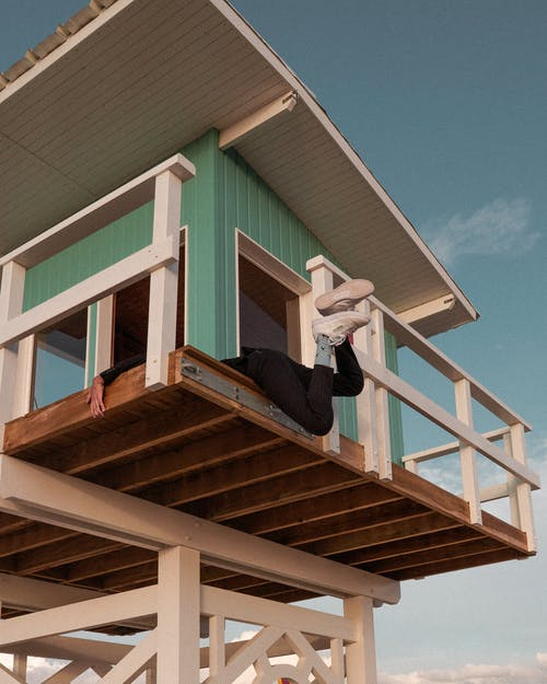 Person in Black Pants With Legs Hanging on Green Wooden House