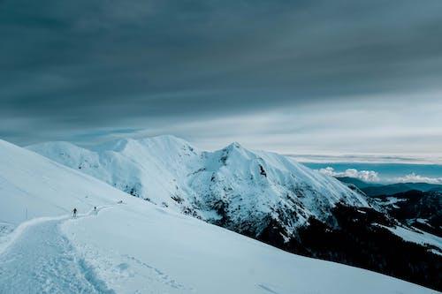 흐린 하늘 아래 눈 덮힌 산의 사진