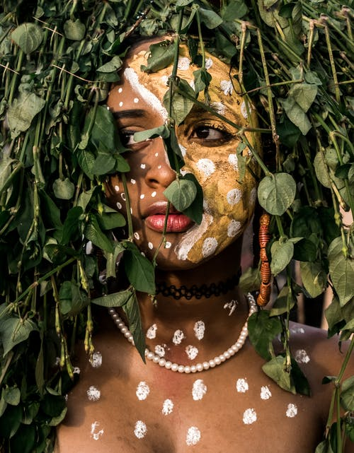 Person With Face Paint Behind Leaves Of A Plant