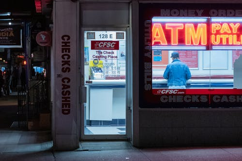 Man in Blue Polo Shirt Standing Inside An ATM Booth