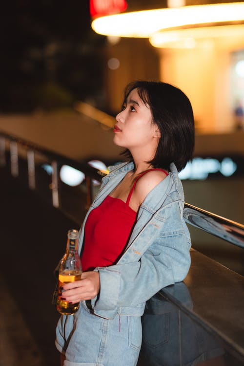 Woman Wearing Blue Denim Jacket While Holding Bottle