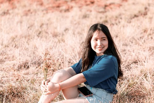 Woman Wearing Blue Shirt While Sitting on Brown Grass Field