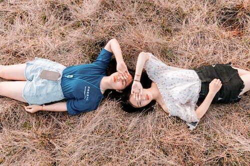 Women Lying Down on Dry Grass