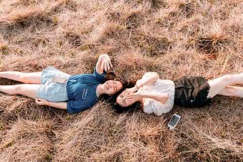 Women Lying Down on Brown Grass While Laughing