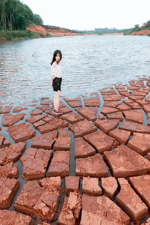 Woman in White Shirt and Black Skirt Standing on Brown Concrete Pavement Near Body of Water