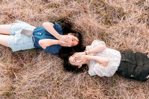 Women Lying on Brown Grass Field While Covering Their Face