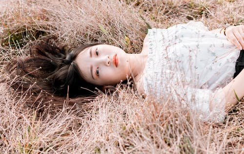 Woman Wearing White Floral Top While Lying on Brown Grass