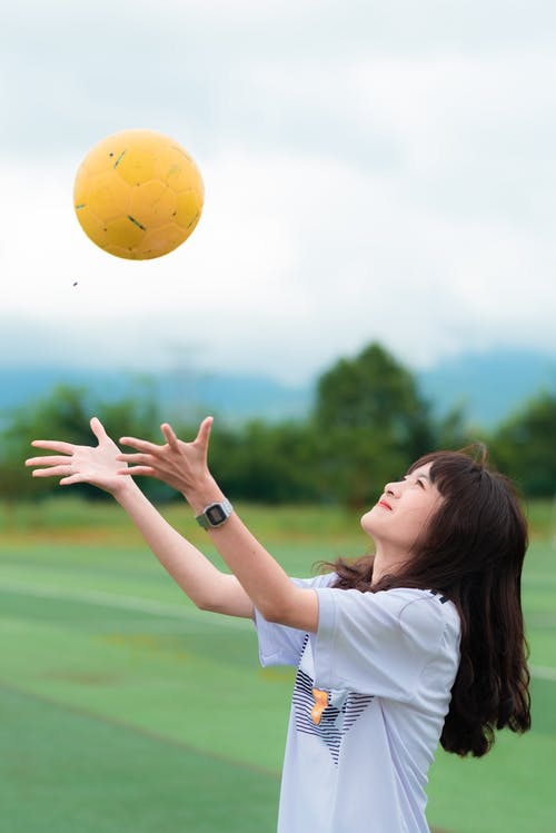 Woman Wearing White T-shirt While Catching a Soccer Ball