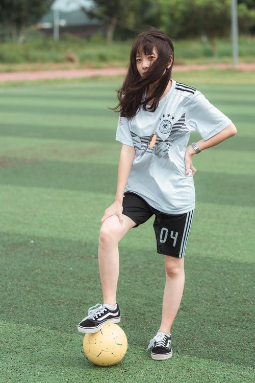 Woman Wearing White Soccer Jersey Shirt and Black Shorts While Standing on Soccer Field