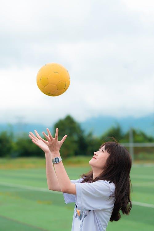 女子接球時穿著白色的t卹