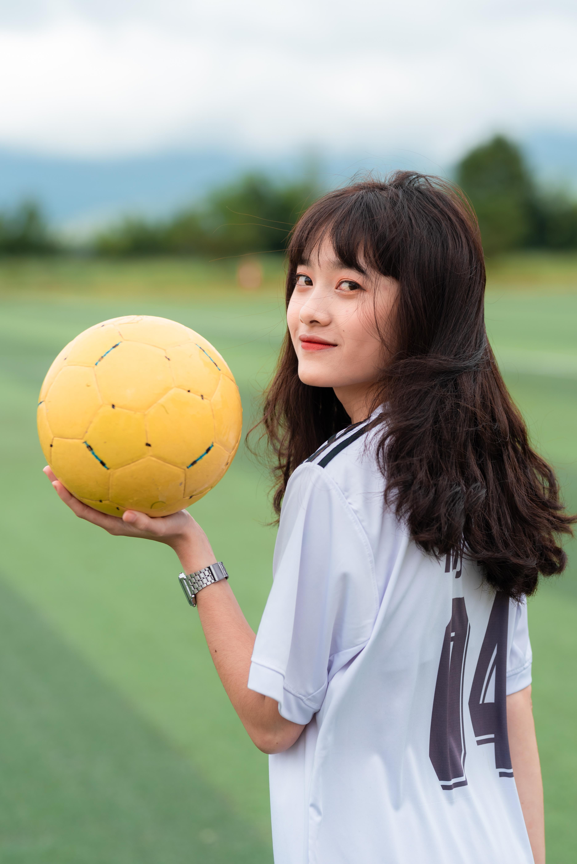 woman wearing white shirt holding yellow soccer ball
