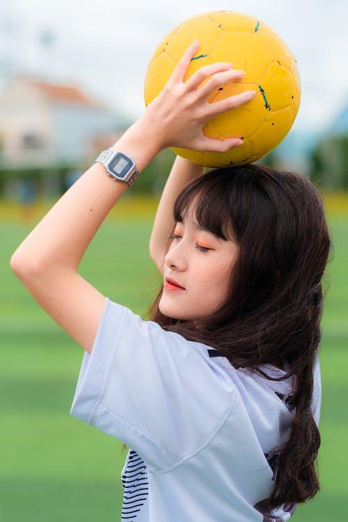 Woman Holding Yellow Soccer Ball