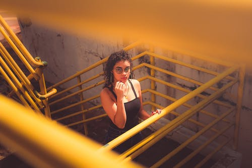 Woman in Black Tank Top and Black Pants Standing on Yellow Metal Staircase
