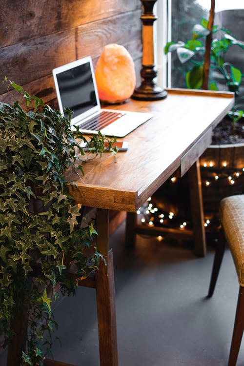 Himalayan Salt Lamp Near Laptop On Wooden Table
