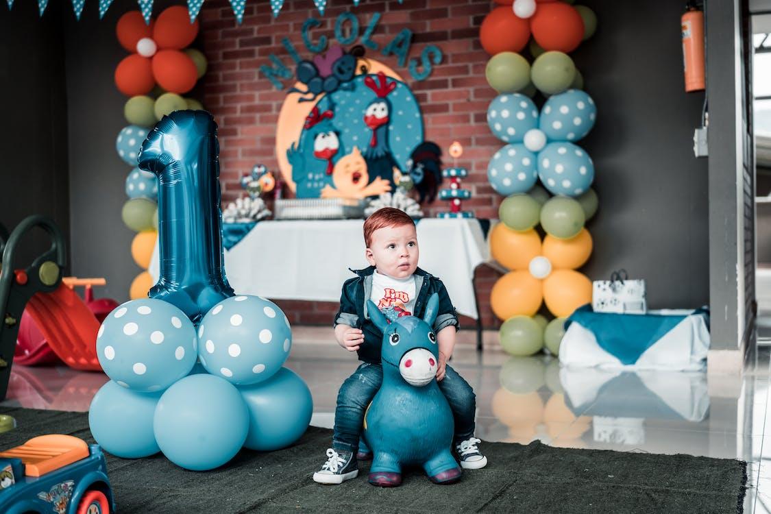 Photo of Child Sitting on Toy Near Balloons